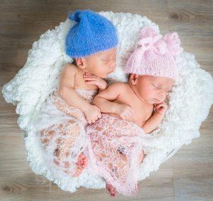 newborn twins - a boy and a girl sleeping in a basket
